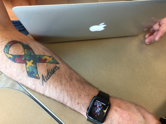 Picture of Ken's autism ribbon tattoo on his left arm.